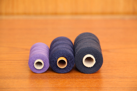 four spools with purple, dark blue and black threads on the table Stock Photo