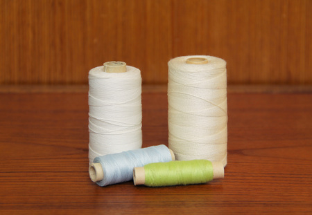 spools with green, blue and white threads on the table