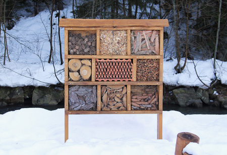 insect hotel for invertebrates filled with various material in winter Stock Photo