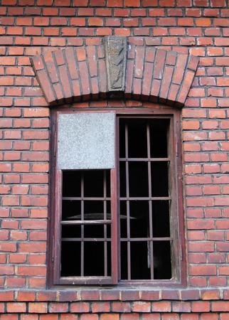 broken window of an abandoned brick house