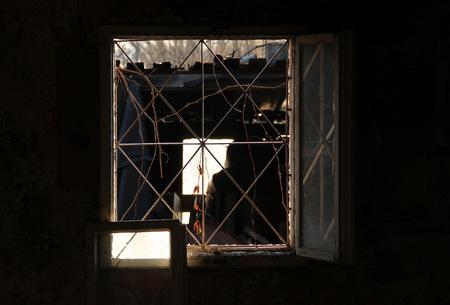 alter Müll, der einem Geist ähnelt, hinter dem Fenster eines verlassenen Hauses