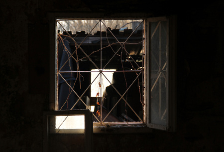 old garbage resembling a ghost behind the window of an abandoned house