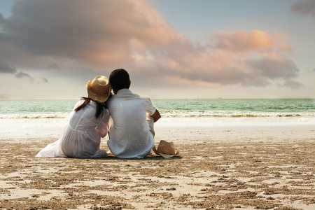 Young couple sitting together on beach photo