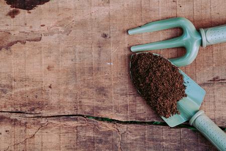 turba: Las herramientas de jardinería y turba en madera tablero de la mesa: Paleta de la jardinería y el tenedor mano Foto de archivo