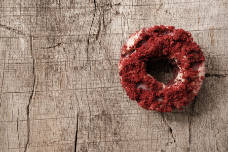 Top view of isolated red velvet donut or doughnut on wooden table, copyspace