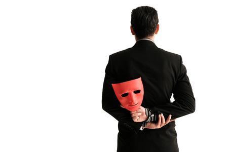 Business man carrying red mask on white background indicating Business fraud and faking business partnership