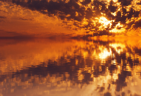 eventide: Crimson sunset by the sea, the suns rays reflected in water