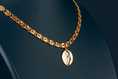 gold pendant on a mannequin on a black background Stock Photo