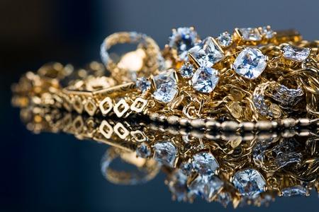 gioielli, oro, pietre preziose su sfondo nero