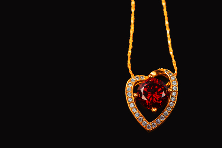 Gold chain with a pendant and a handmade ruby on a black background