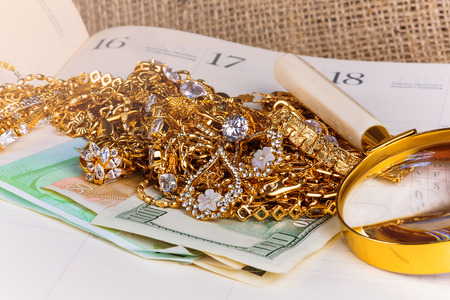 gold jewelry and money on business diary
