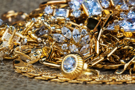 gold jewelry with precious stones on sackcloth