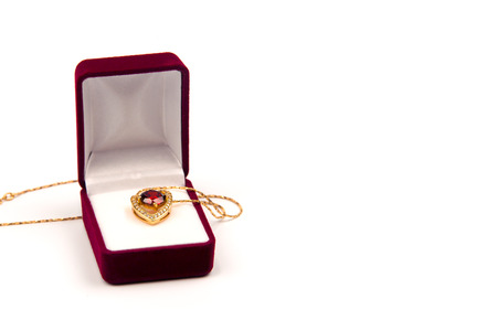 Gold heart pendant with precious stones in a red gift box on white background isolated Reklamní fotografie