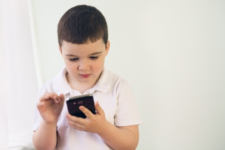 boy shows on tablet computer pointing with finger Imagens