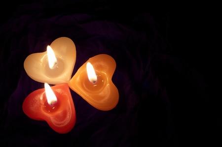 backcloth: Coloured candle shaped heart on black backcloth Stock Photo