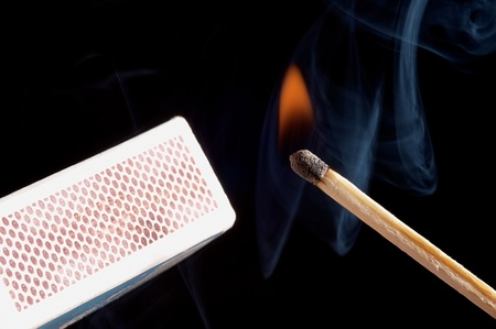 Lighted match on a black background photo