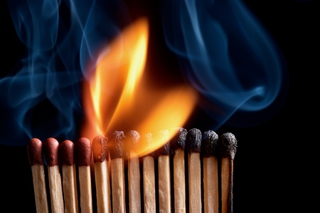Burning matchstick on black background photo