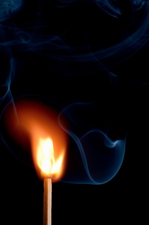 ignited: Burning matchstick on black background