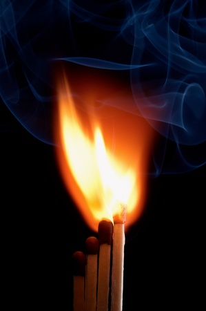 Burning matchstick on black background