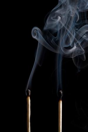 Smoking matches on black backcloth photo