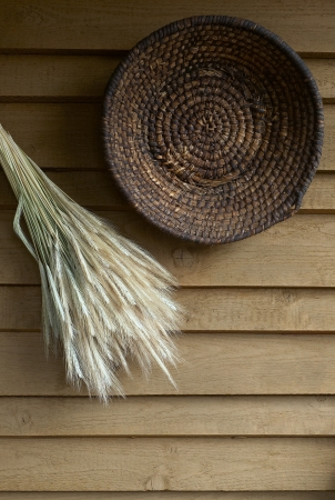 baskets with cereal ears hangs on a wooden tile photo