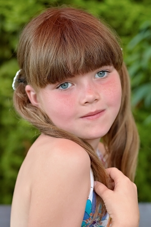 freckled: Portrait of young girl holding a pigtail Stock Photo