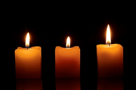 three lit candles on a black background Stok Fotoğraf