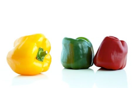 differently: three differently colored peppers on a white background