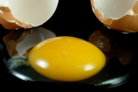 yolk to the shell on a black background photo