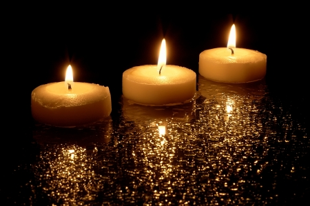 three lit candles on a black background photo