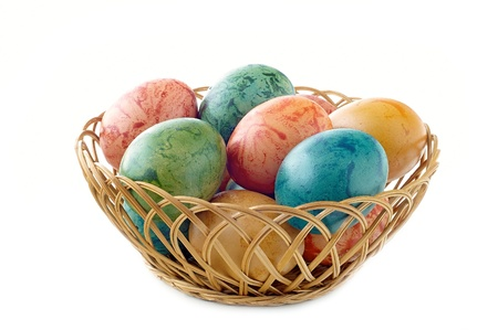 Easter eggs in a wicker basket on a white background photo