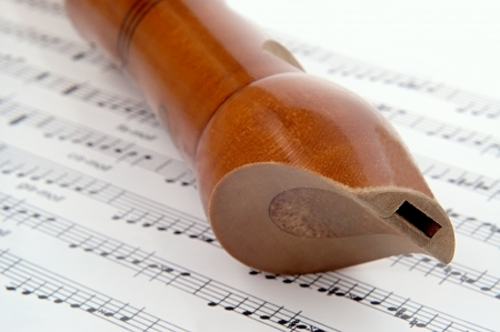 wooden flute lying on musical notation photo