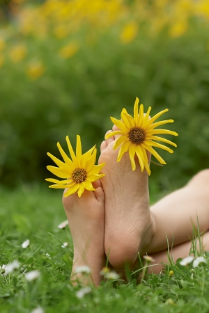 Yellow flowers between your fingers on legs photo