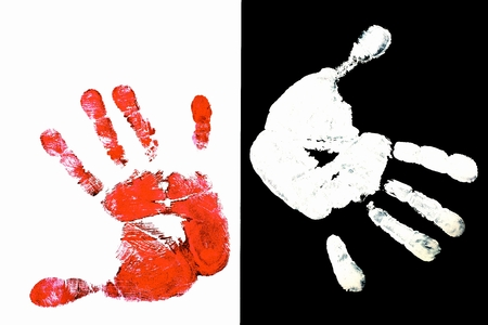Detailed view of a red hand print on a white background and white hand on black background photo