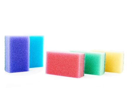 Different colored sponges on white background photo