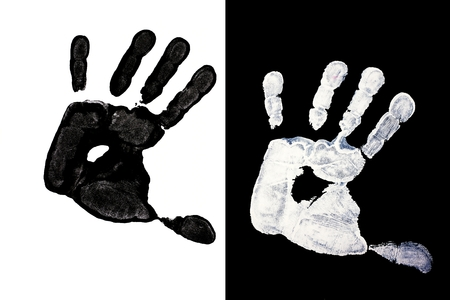 Detailed view of a black hand print on a white background and white hand on black background photo