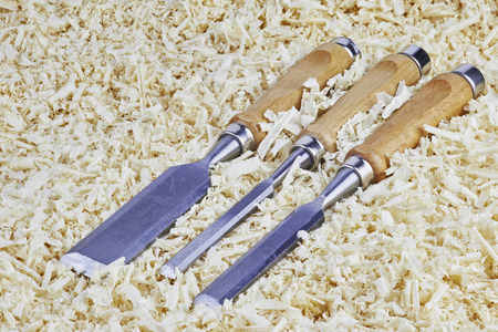 pointed arm: Three chisels of various widths lying in wooden shavings