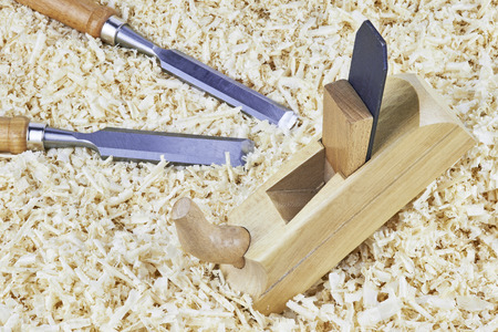 pointed arm: Two chisels and one spokeshave lying in wooden shavings