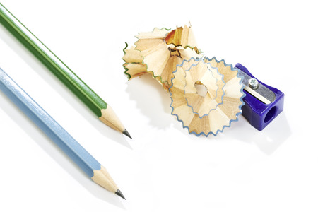 pencil sharpener: Blue plastic pencil sharpener with shavings and two pencils on white