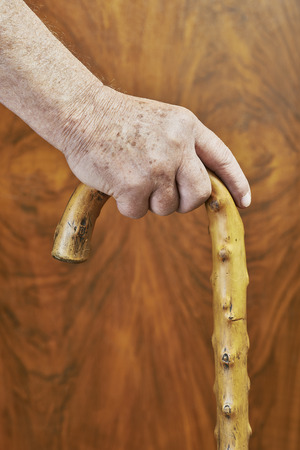 wooden stick: An old man holding a wooden stick Stock Photo