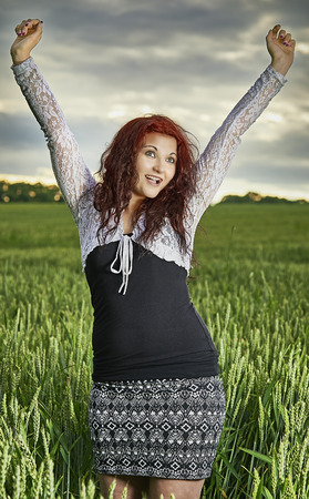 wench: Young girl standing in a cornfield with sky in the background