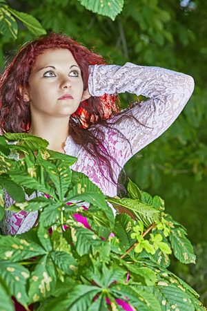 wench: Young girl standing near the green leaves of the tree chestnuts