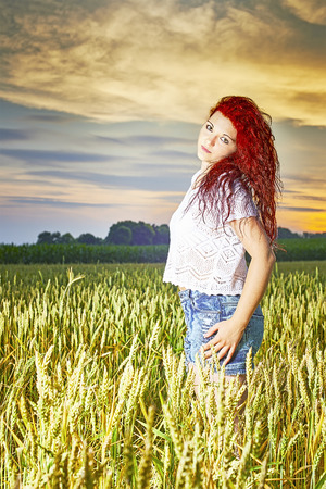 czech women: Young girl standing in a cornfield with sky in the background