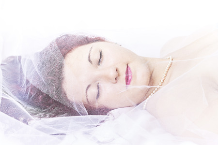 wench: Young girl lying under a mesh fabric with a white background Stock Photo