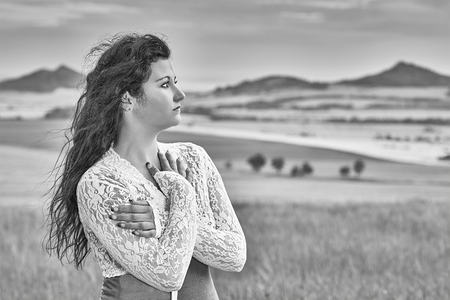 wench: Young girl standing in a cornfield with a landscape in the background