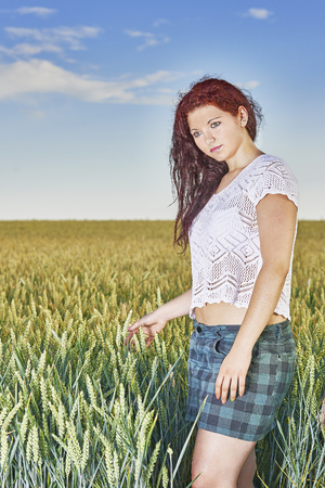 wench: Young girl standing in wheat field with sky in the background Stock Photo