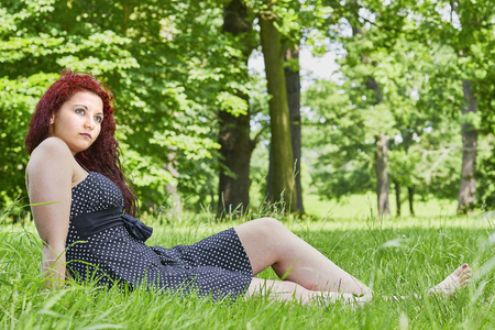 wench: A young girl sitting in the grass with trees in the background