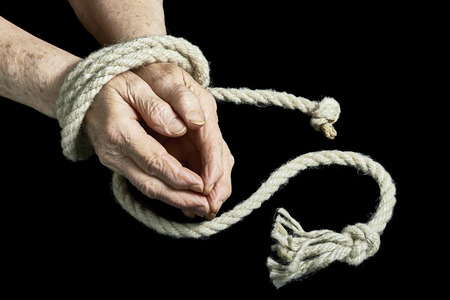 View of the old hands tied with rope on a black background