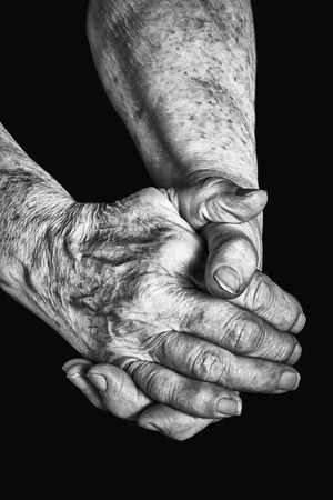 clasped: Old woman clasped in her hands on a black background