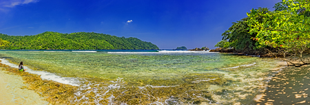 Panorama sunny view of an Indonesian beach with sand and sea on the background of forested mountains